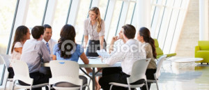 8 people round table, not socially distanced or masked. They appear to be addressed by one person and all look pleasant
